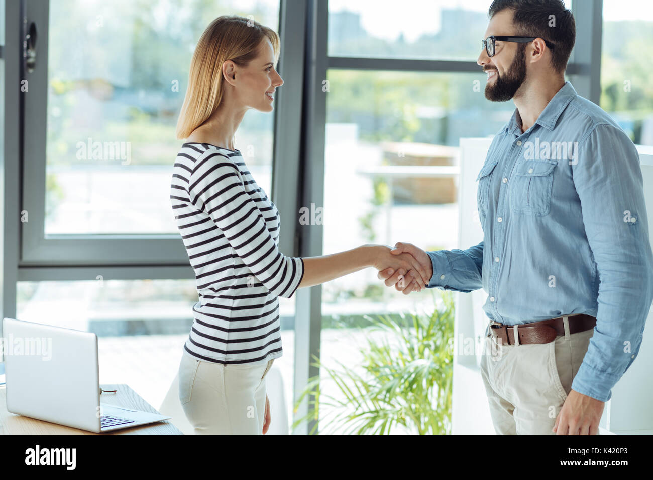Pleasant man and woman giving each other a handshake Stock Photo