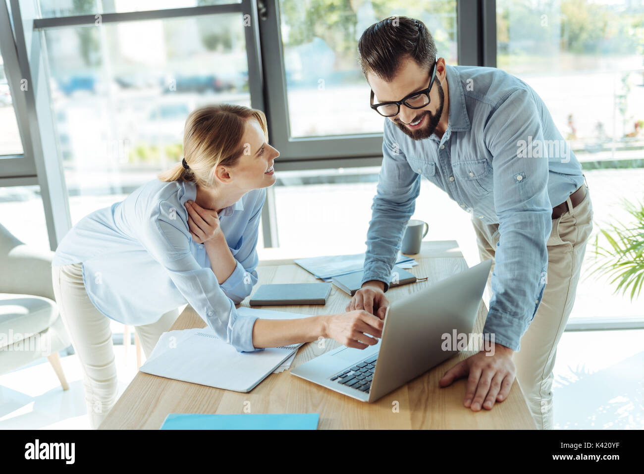 Pleasant colleagues watching a video tutorial on laptop - Stock Image