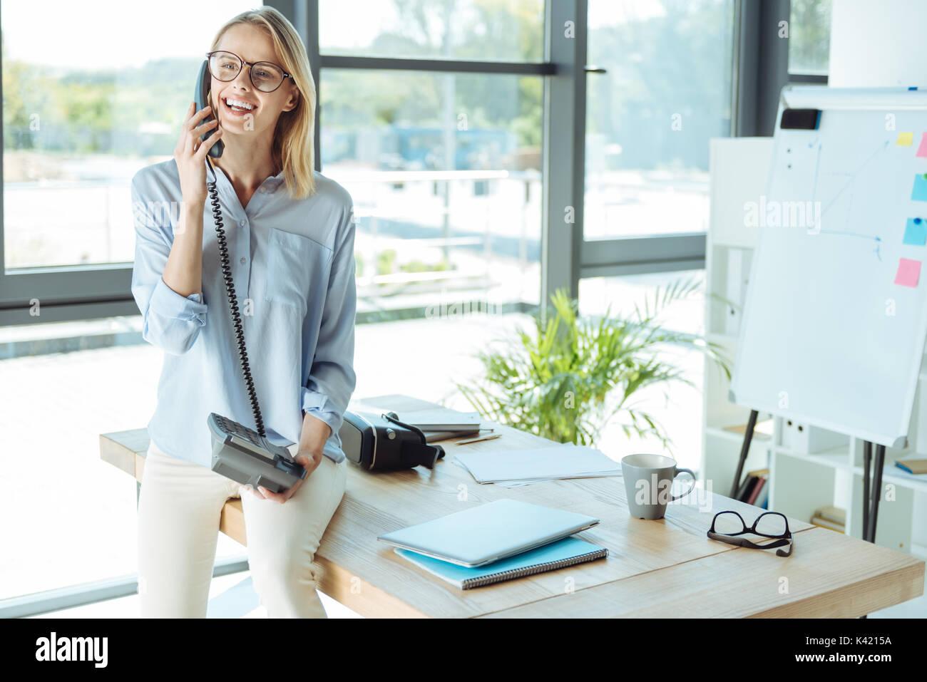 Joyful pretty woman talking on the landline phone in office - Stock Image