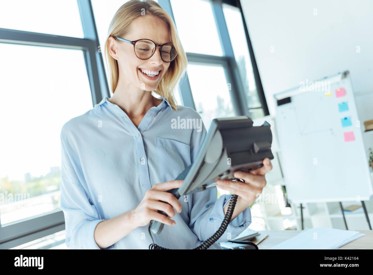 Joyful woman making a call on a landline office phone - Stock Image