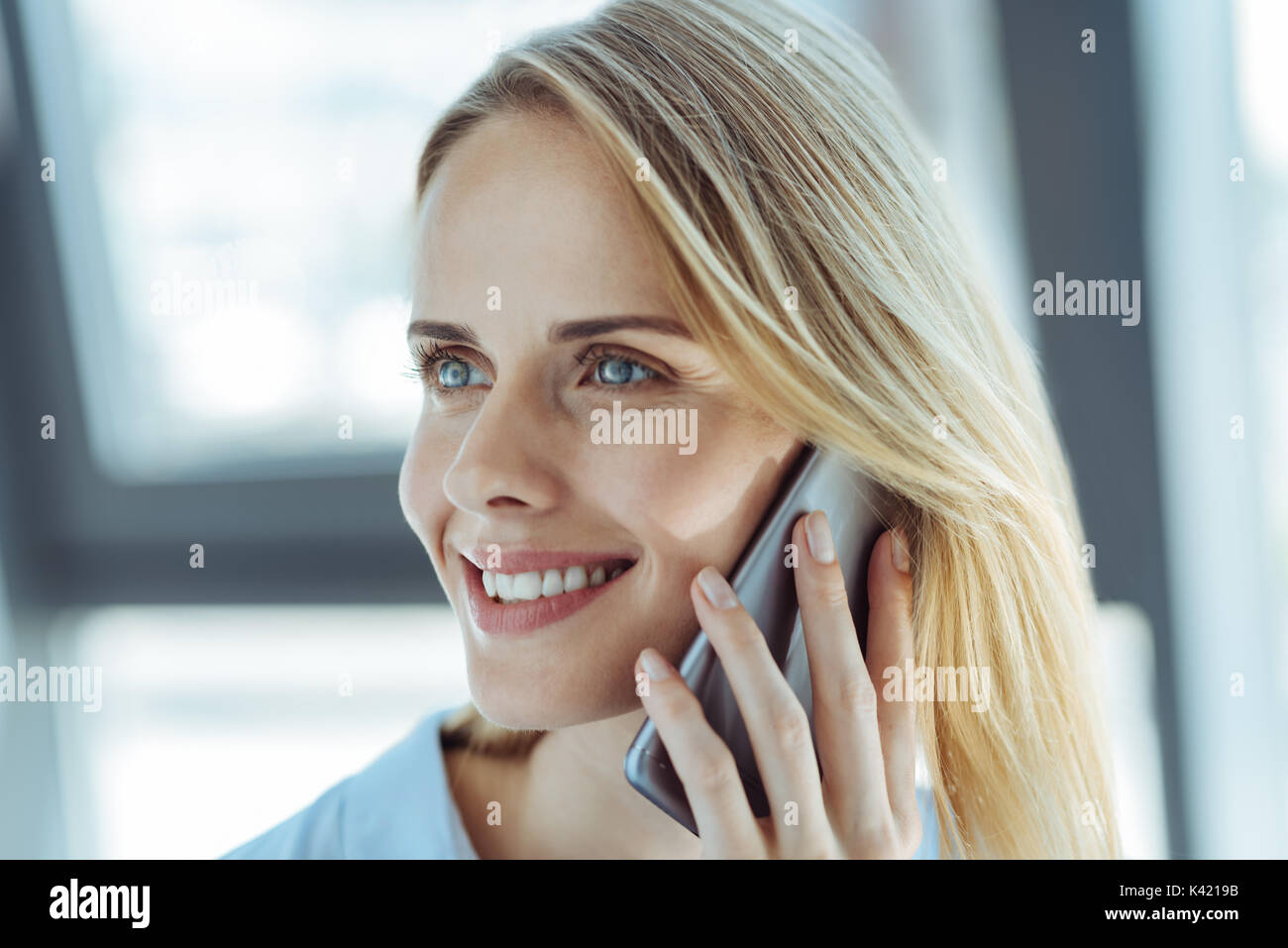 Happy woman having a conversation on the phone - Stock Image