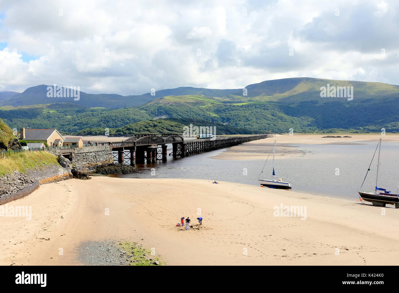 Barmouth, Wales, UK. August 05, 2017. The wooden railway bridge over the river Mawddach with a train and holidaymakers Stock Photo