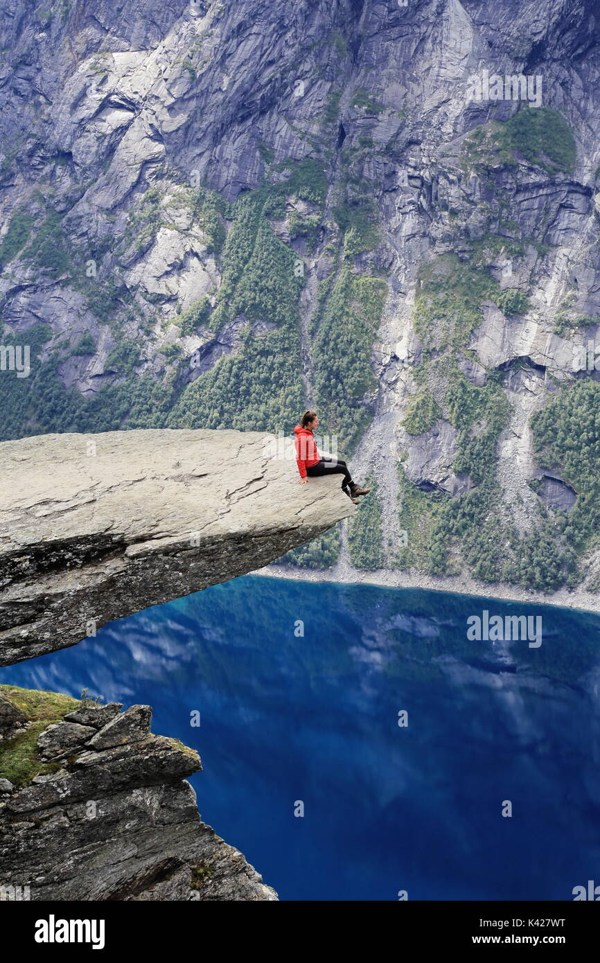 Woman Hiker enjoying view from Trolltunga rock formation in Norway - Stock Image