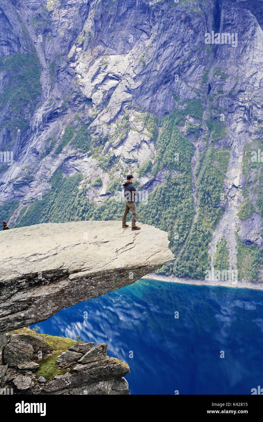Hiker enjoying view from Trolltunga rock formation in Norway - Stock Image