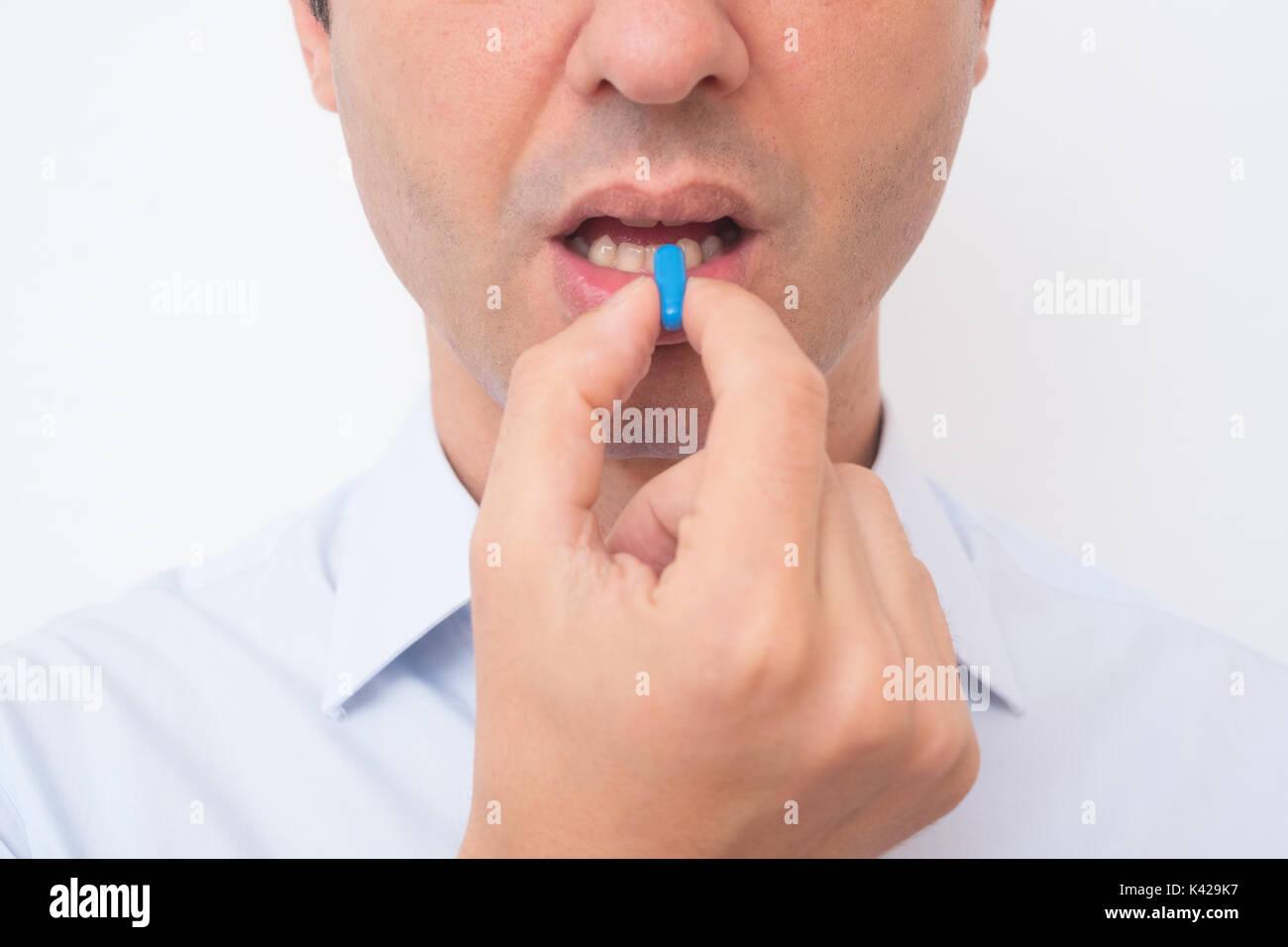 Head of sick man eating blue medicine pill - Stock Image