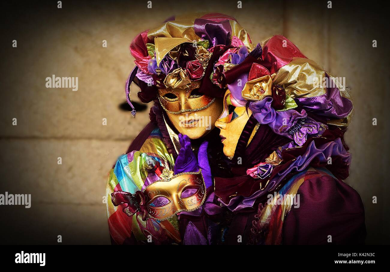 A couple with matching costumes, mostly in purple and bright colours, wearing masks at the Carnival of Venice - Stock Image