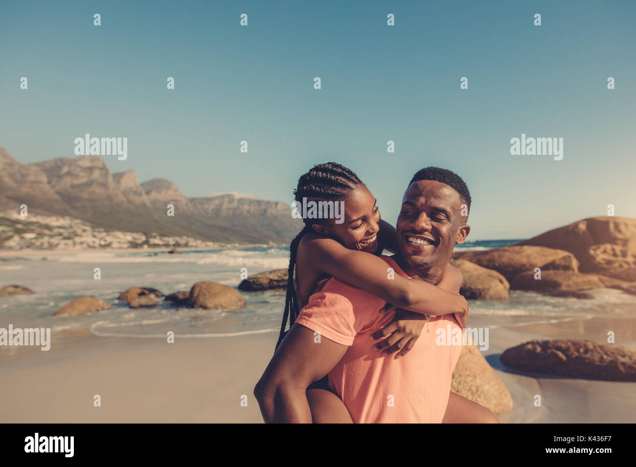 Handsome african man giving piggyback ride to his smiling girlfriend at the beach. Couple enjoying themselves at the seashore. - Stock Image
