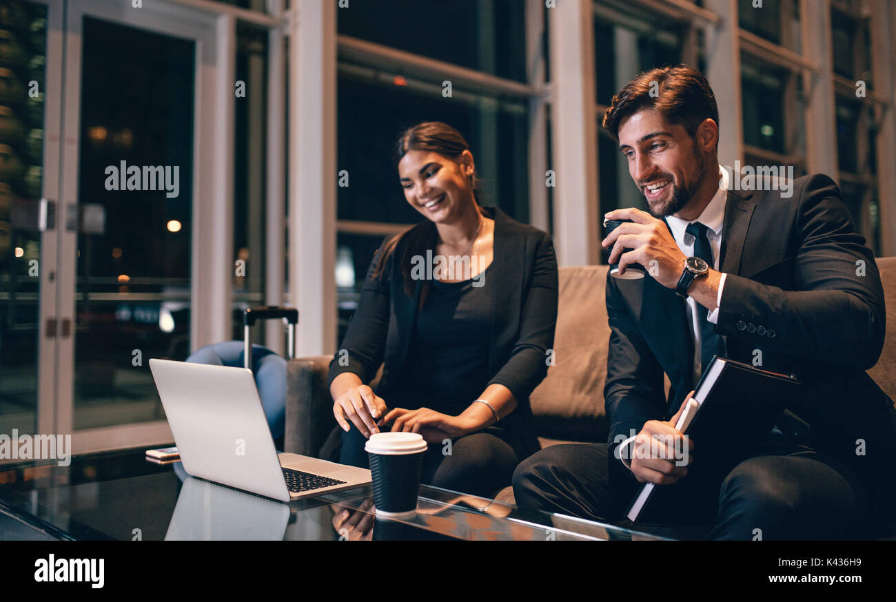 Young businessman and woman waiting at airport lounge and looking at laptop. Business travelers waiting for their flight at airport terminal. - Stock Image