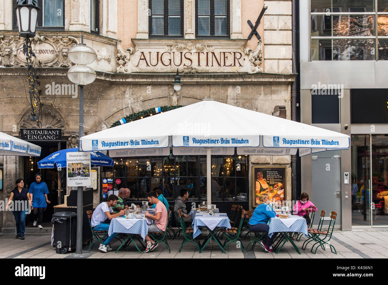 Tourists seated at tables outside the historic Augustiner beer hall, Munich, Bavaria, Germany - Stock Image