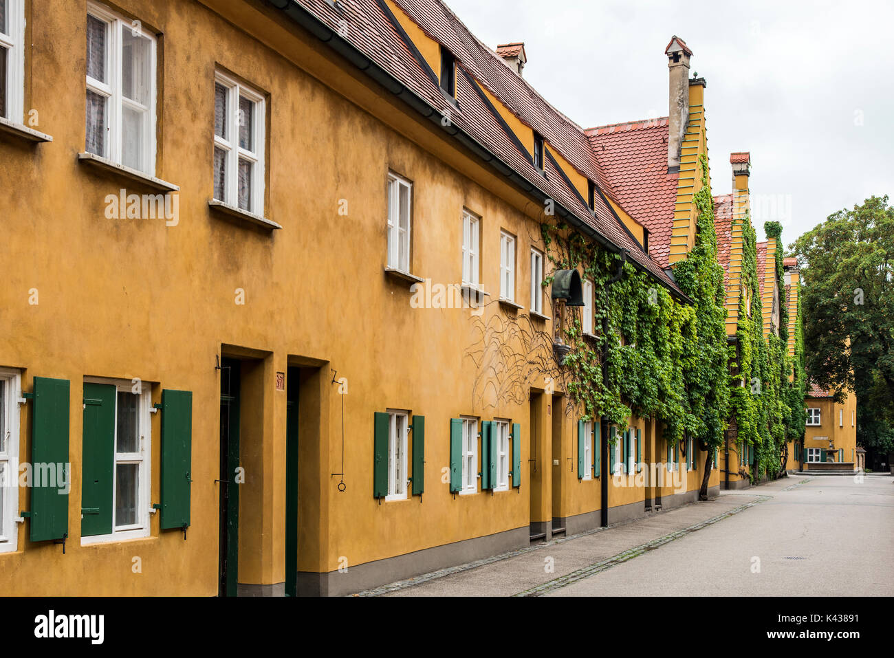 Street view of the Fuggerei settlement, the world's oldest social housing complex still in use, Augsburg, Bavaria, Germany - Stock Image