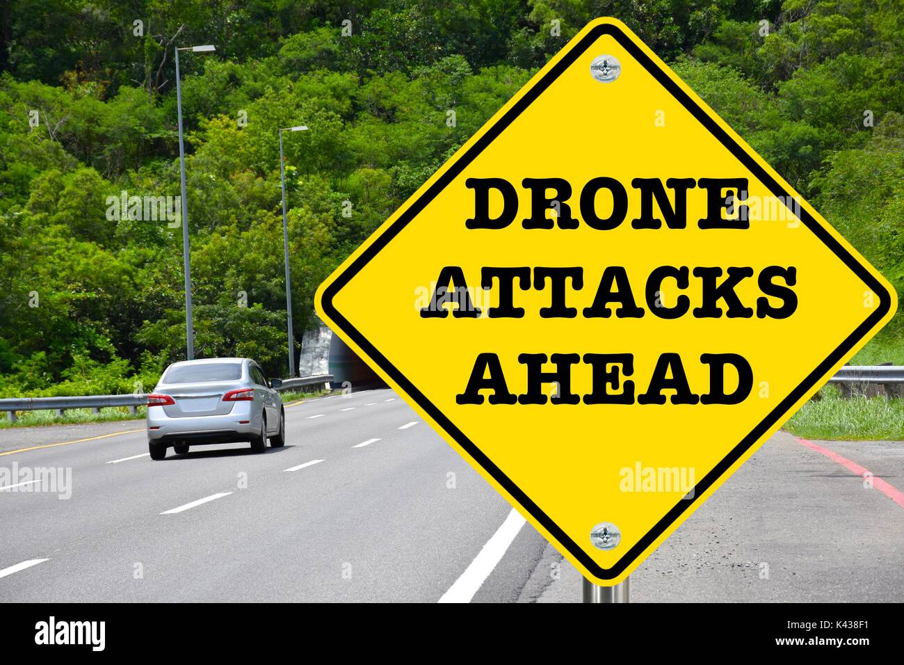 Drone attacks ahead, yellow warning street sign - Stock Image