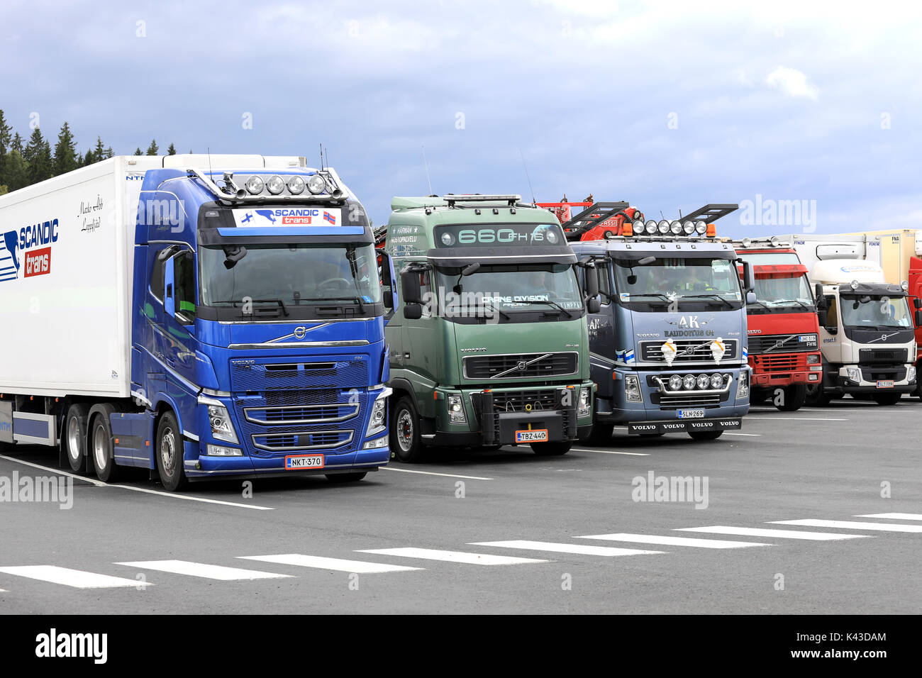 FORSSA, FINLAND - AUGUST 25, 2017: Colorful Volvo trucks parked on the asphalt yard of a truck stop on a cloudy day. - Stock Image