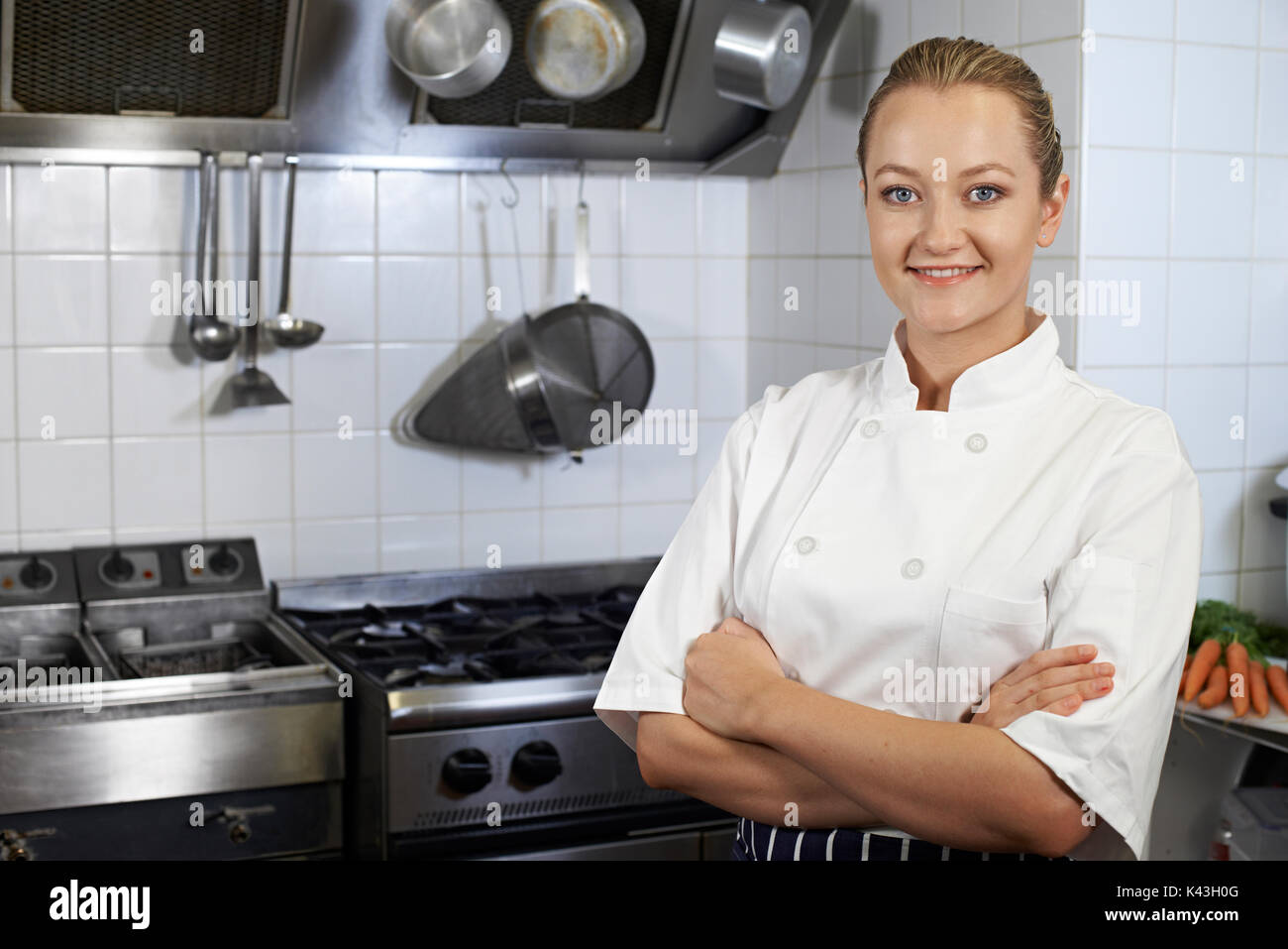Portrait Of Female Chef Standing In Kitchen - Stock Image