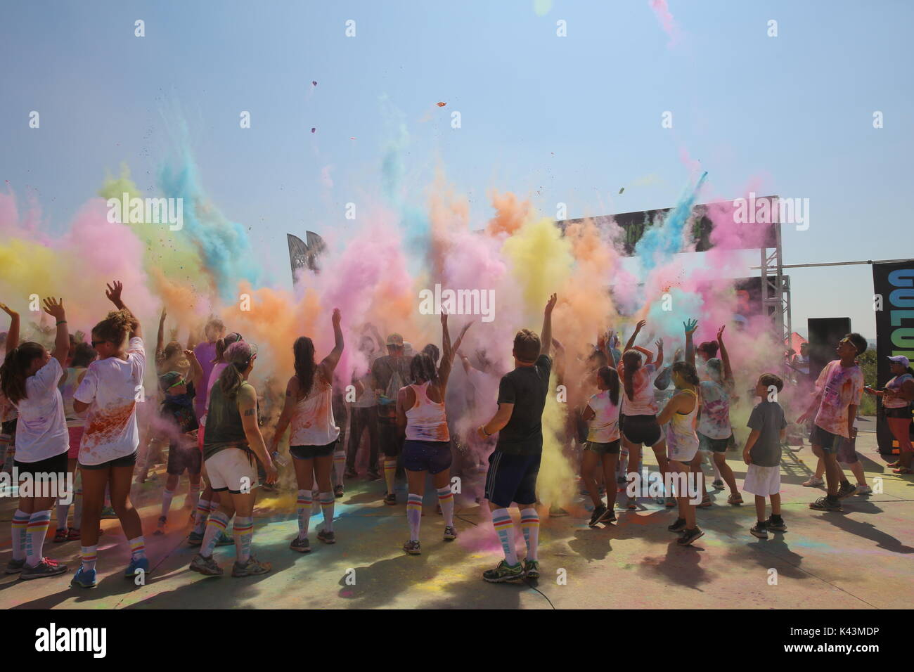 Runners throw color bombs in the air after complete the Color Me Rad 5K marathon run at the Marine Corps Air Station Miramar August 22, 2015 in San Diego, California.  (photo by Kimberlyn Adams via Planetpix) - Stock Image