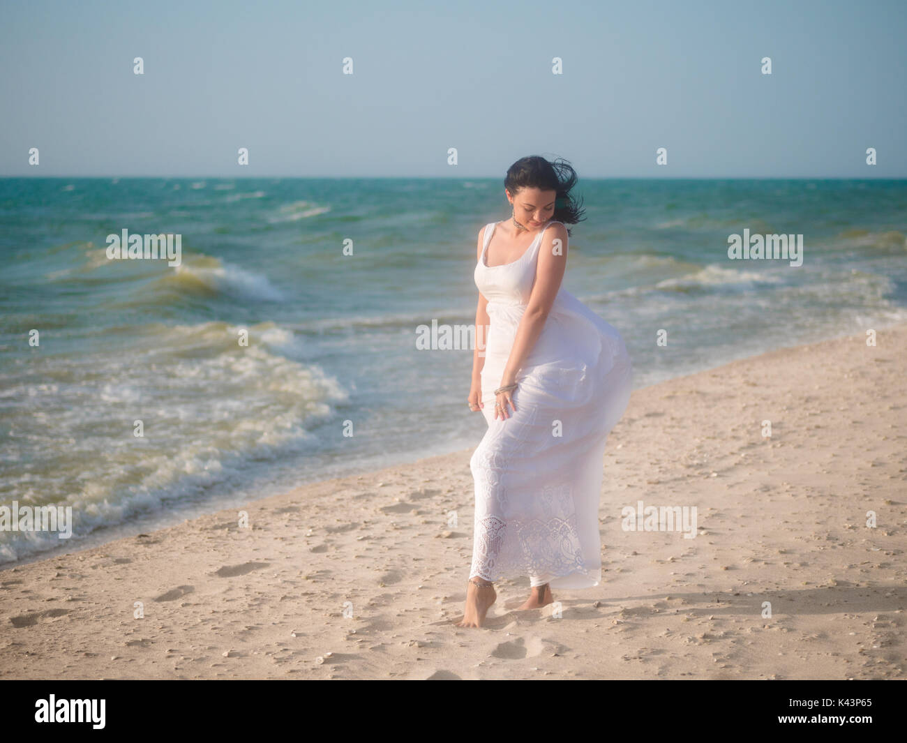 The young girl enjoys good windy weather on sea beach. Woman is dressed in white sundress and boho jewelry rest Stock Photo
