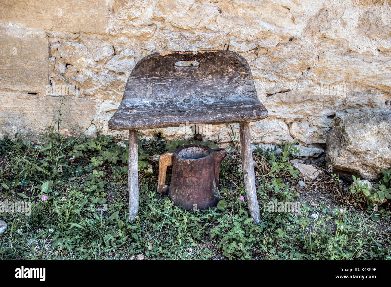 Countryside, East Serbia - Antique three legs stool and wooden wine jug in front of old vinery stone wall Stock Photo