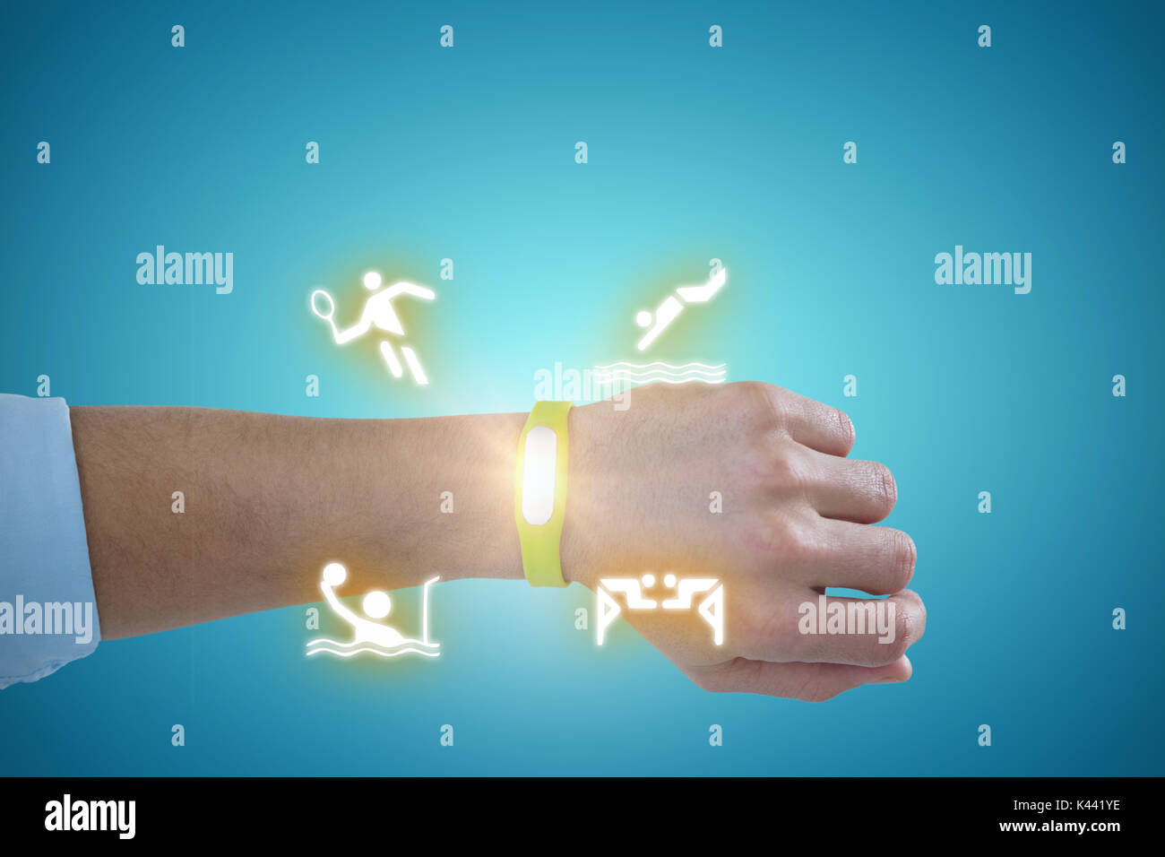 Hand of man wearing green fitness band against blue vignette background - Stock Image