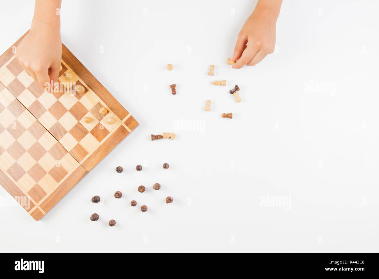 Top view of kid hand and chess board with chess pieces - Stock Image
