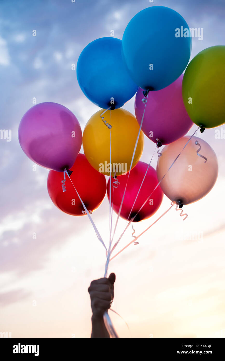 Man Hand Holding Colorful Balloons And A Beautiful Sunset Birthday Party