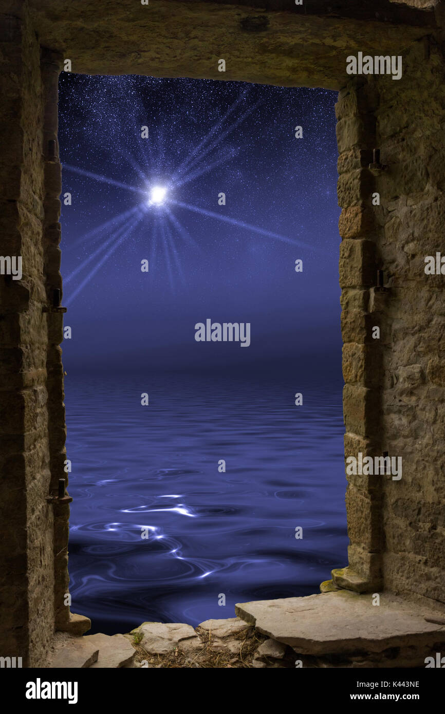Bright star with rays on the dark night sky covered by other stars with wavy water surface which reflects all the pattern visible through an old ancie - Stock Image