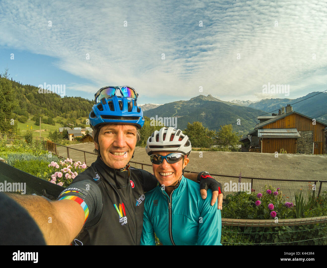 Cycling Mountains Alps Couple Cyclists Selfie Bike riding bikewear cycle helmets on sunglasses panoramic landscape view over the valley clouds pattern - Stock Image