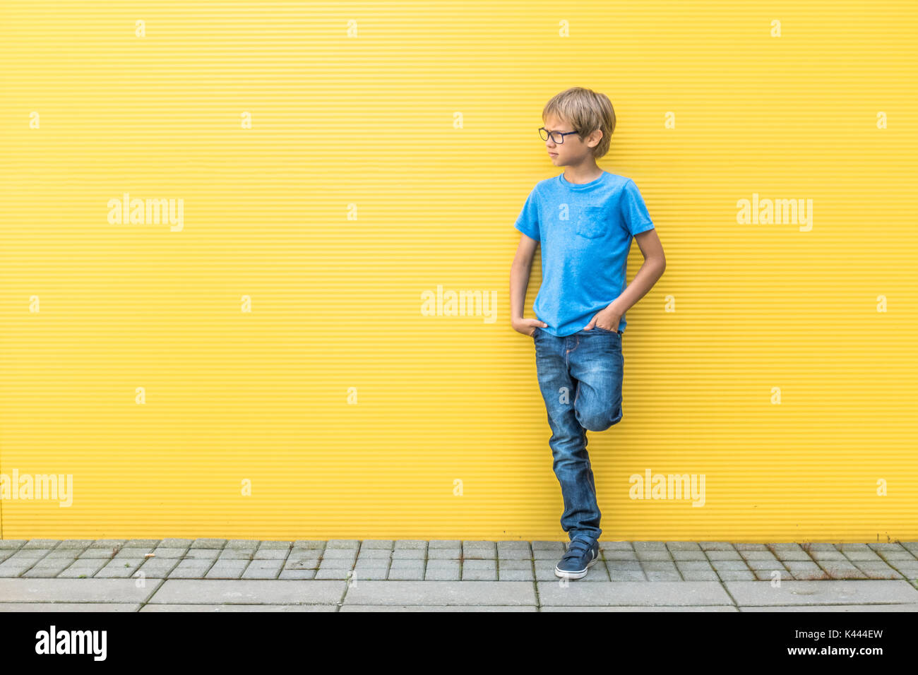 Boy with glasses standing near yellow wall oudoors - Stock Image