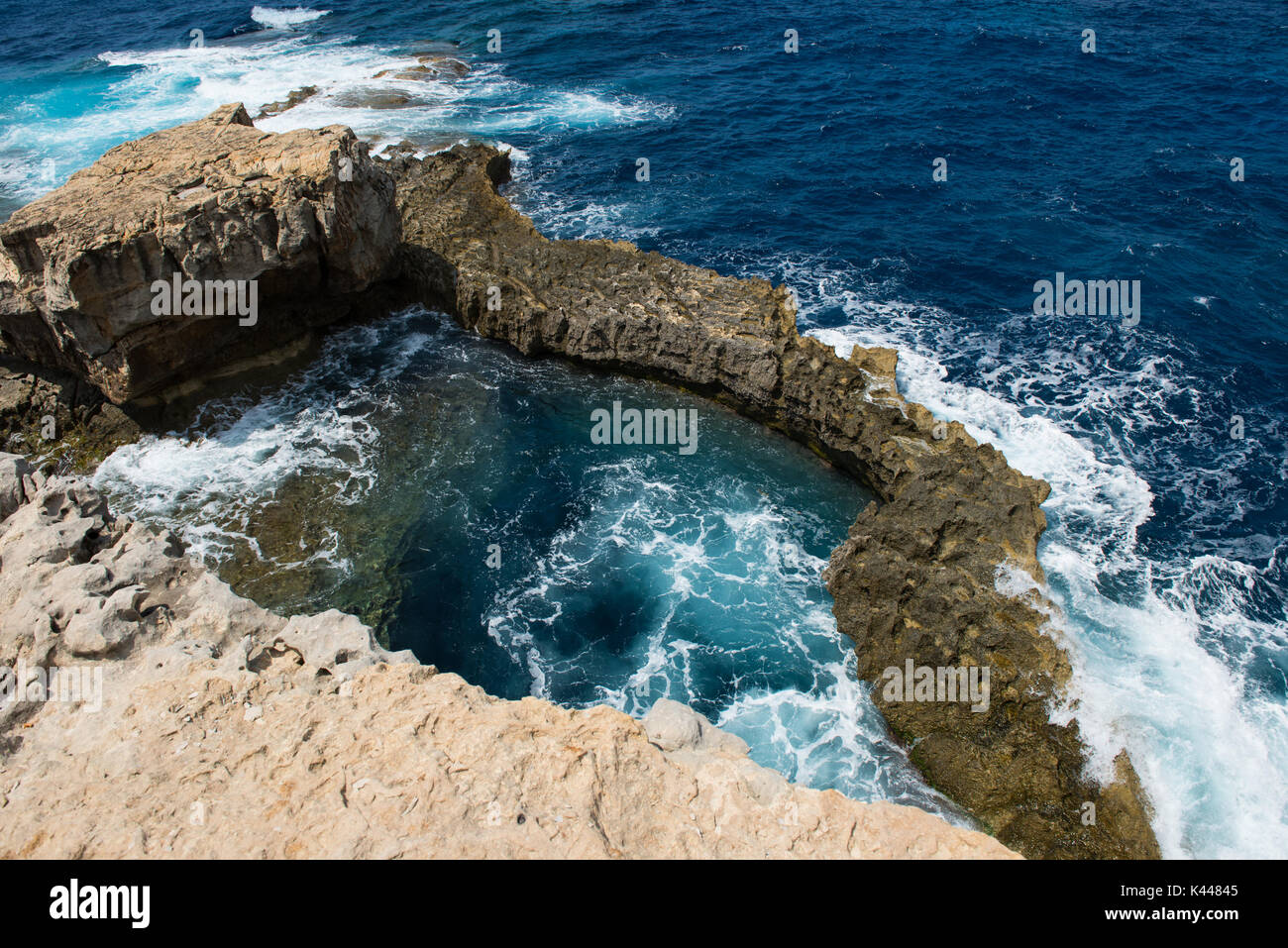 Rocky coastline and sea. Blue hole and the collapsed Azure window in Dwejra Bay, Gozo, Malta - Stock Image