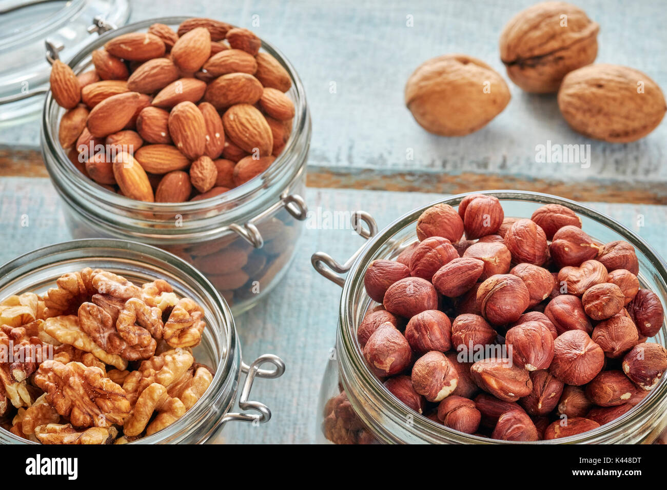 Walnuts, hazelnuts and almonds in jars on a rustic wooden background, shallow depth of field. - Stock Image