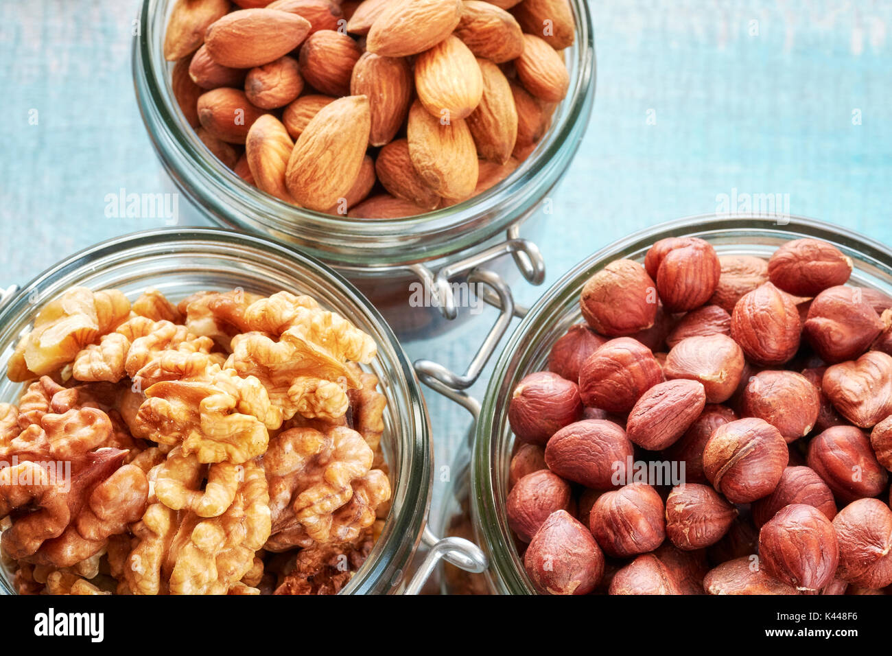 Walnuts, hazelnuts and almonds in jars on a rustic wooden background. - Stock Image
