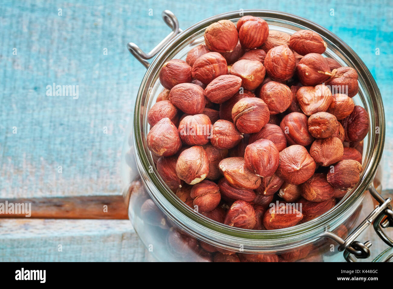 Hazelnuts in a jar on a rustic wooden background, space for text, shallow depth of field. - Stock Image