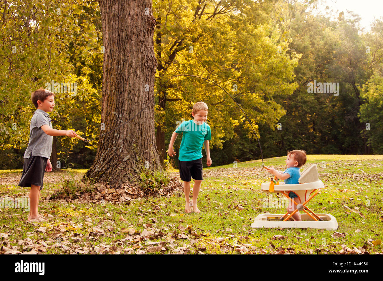 two boys playing jump rope with their baby brother - Stock Image