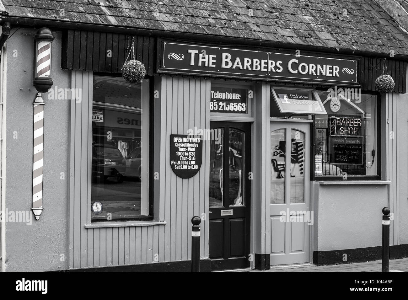 Barber Shop Front with Red and White Pole in Co.Clare Ireland in black and white - Stock Image