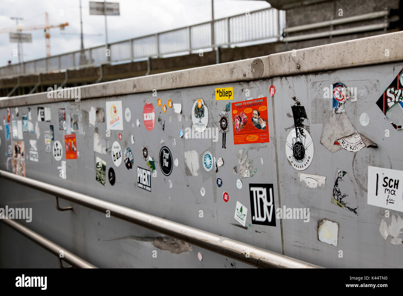 The walls and walkway outside the Electronica Centre, Linz, Austria are defaced by being covered in thousands of paper stickers. - Stock Image