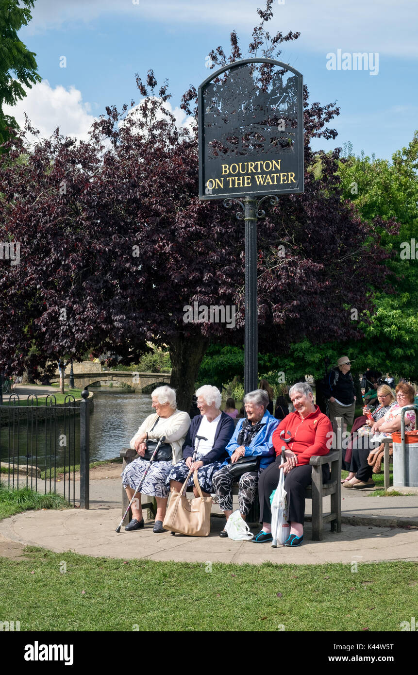 A group of pensioners enjoying sitting on a bench beside the river Windrush, below the Bourton on the Water sign in the centre of the historic village - Stock Image