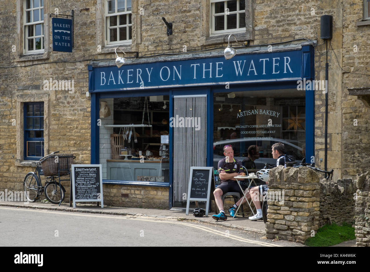 Cycling tourists enjoying the Summer Sun, a coffee & a snack outside an artisan bakery in the historic Cotswold village of Bourton on the Water - Stock Image