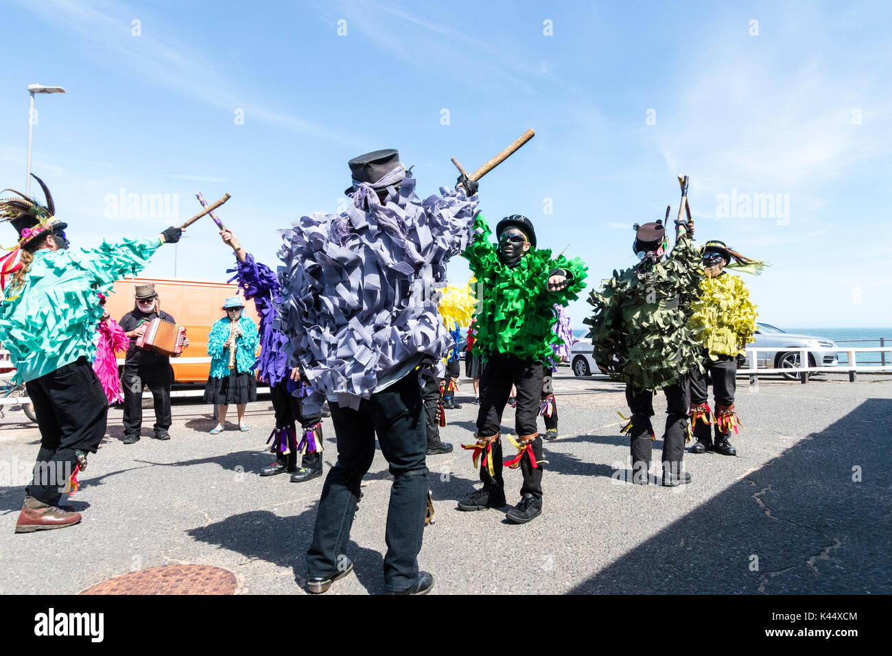 Traditional morris men wearing top hats and tatter jackets in various colours dancing holding wooden poles on Broadstairs sea front. Summertime. - Stock Image