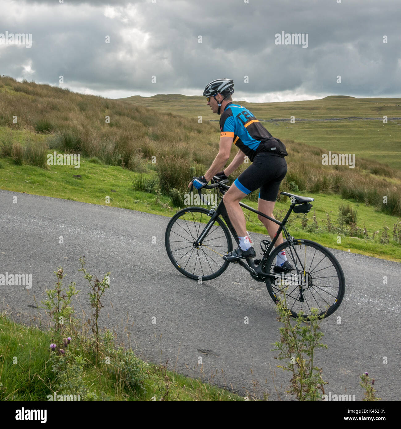 Cyclist, out of the saddle, ascending a steep uphill section of road on a Cube road bike with Di2 electronic groupset on Brootes Lane, Malham Moor, UK - Stock Image