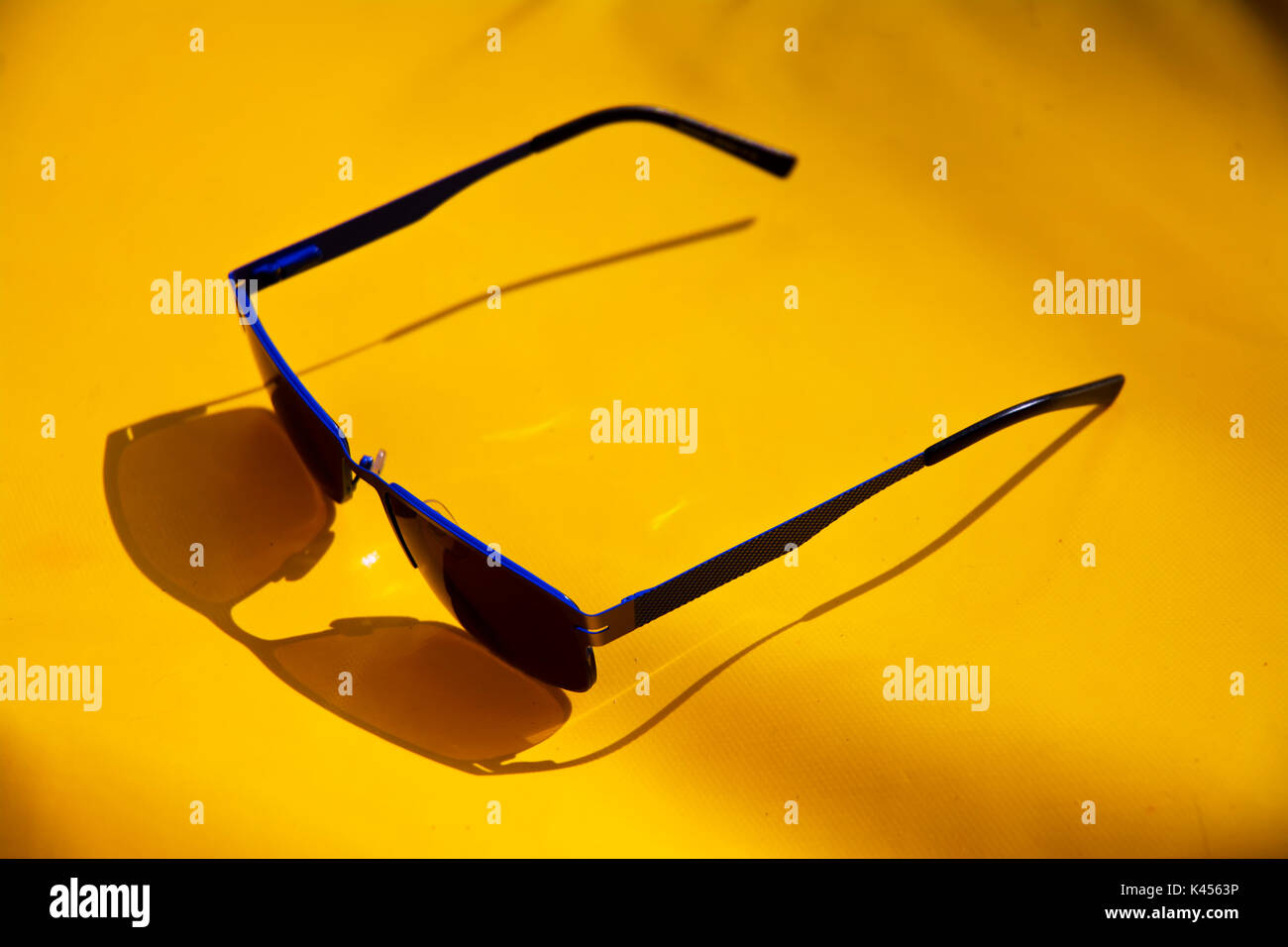 Blue Sunglasses on a yellow Sunbed - Stock Image
