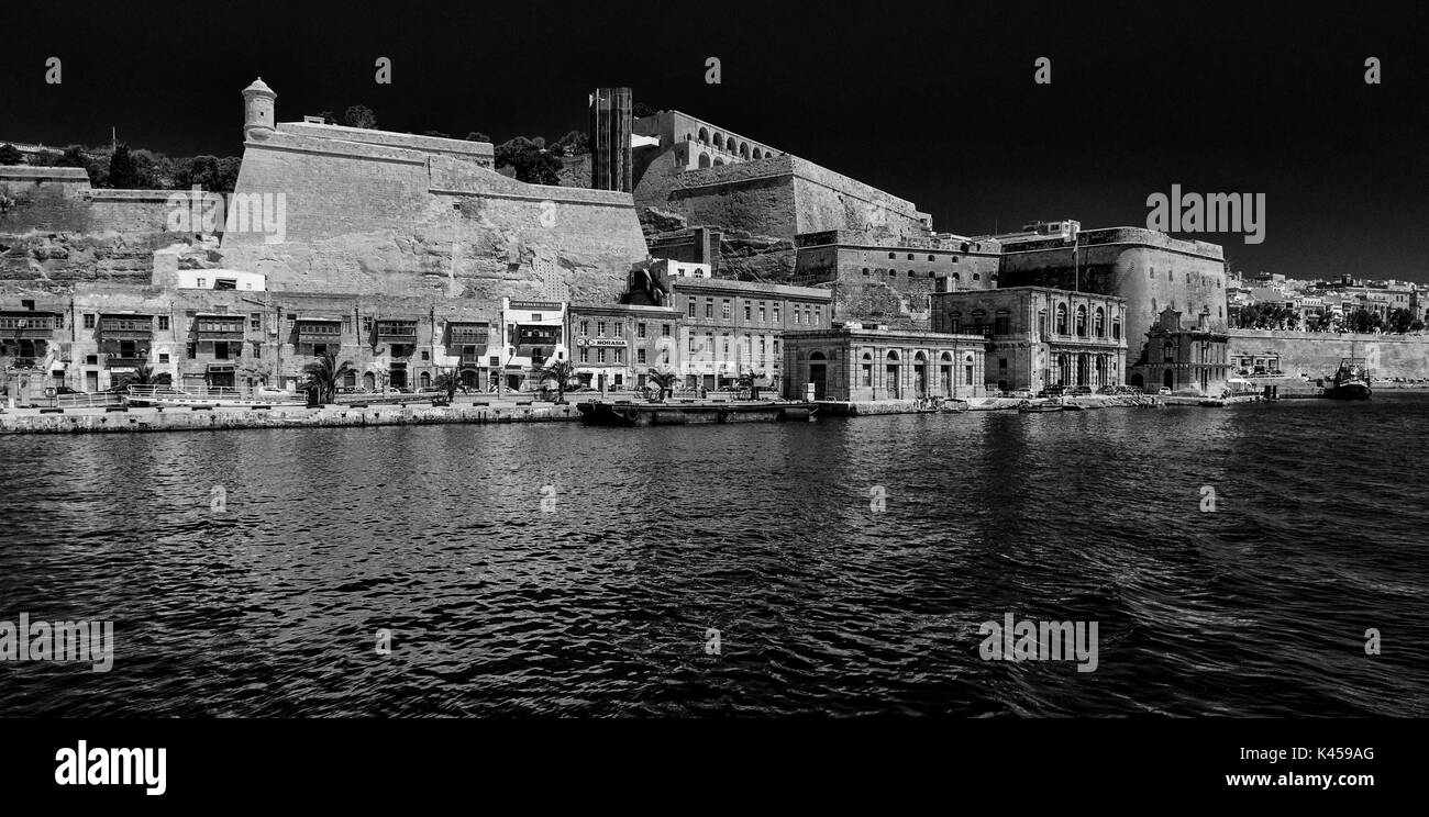 Black and white photograph of the Valletta waterfront, Malta, from the Grand Harbour, looking towards the Upper Barrakka Gardens - Stock Image