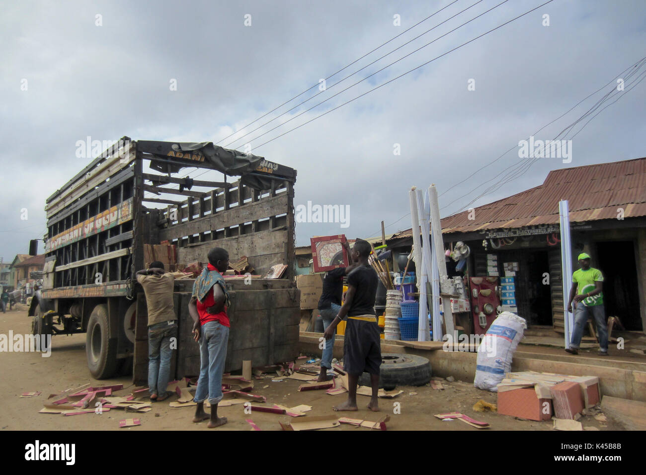 Some boys in the street next to an old wooden truck in the large city of Lagos, Nigeria - Stock Image