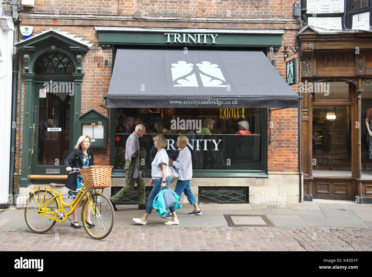 Historical buildings in the fine city of Cambridge, England. Trinity restaurant in the town centre, linked to the colleges as people walk past - Stock Image