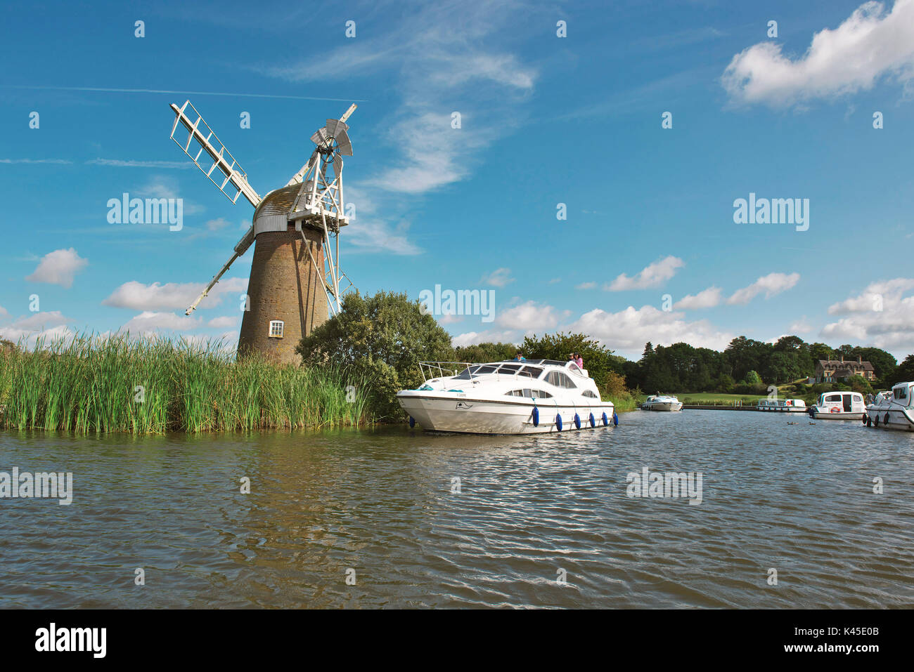 Lovely Broads cruiser on the river ant at How Hill in front of Mill on a bright summers day - Stock Image