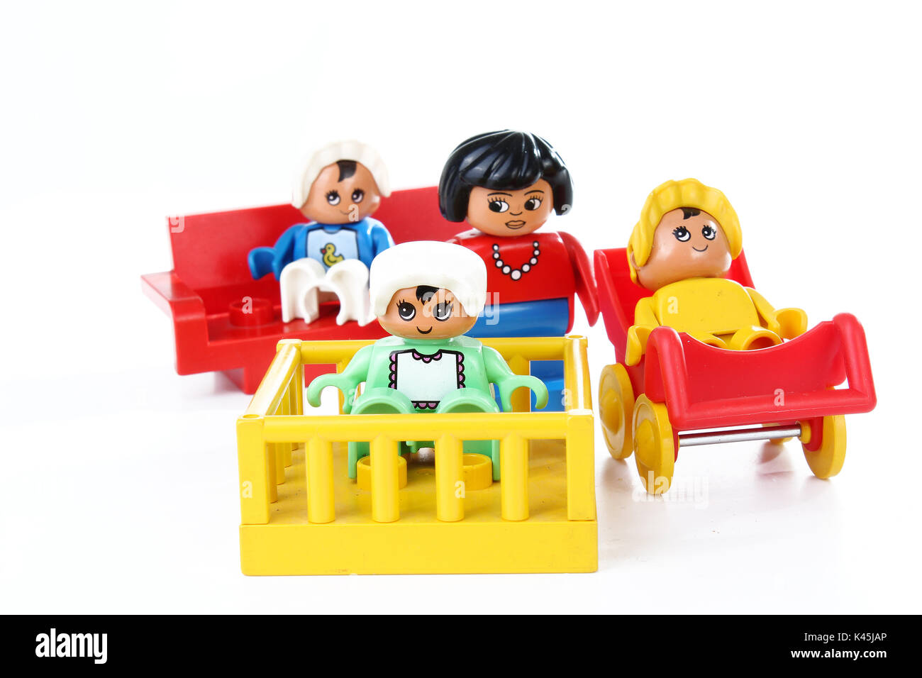 Lego Duplo illustration about single mom with three childrens / baby. Mother or babysitter with kids babies toy on isolated white studio background. - Stock Image