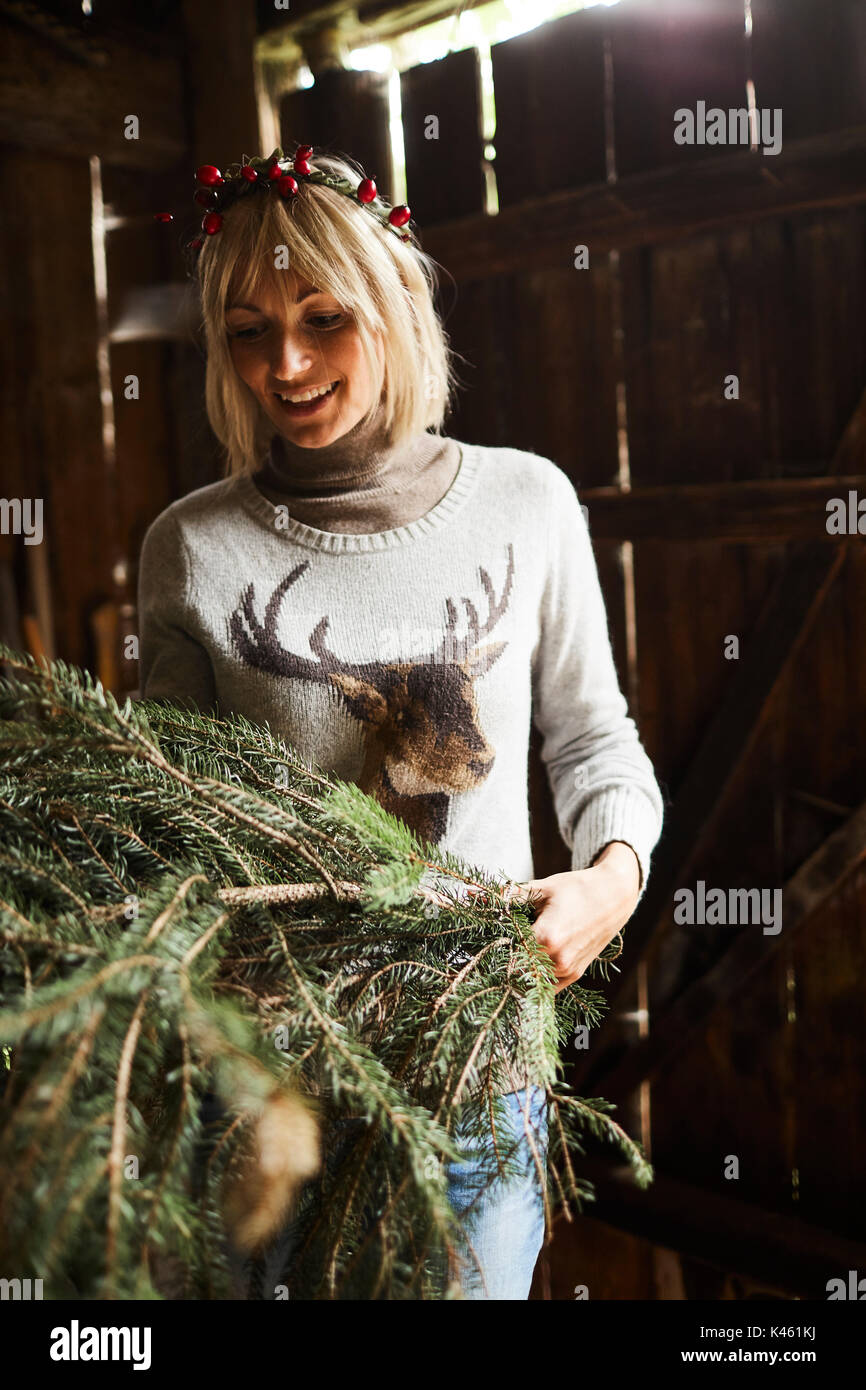 Blond woman, headdress, garland with rose hips, twigs of evergreens for decoration - Stock Image