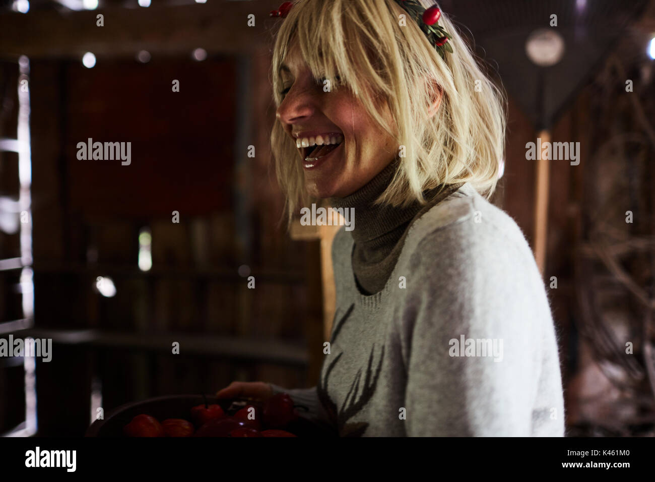 Blond woman, headdress, garland with rose hips, laugh, side view, - Stock Image