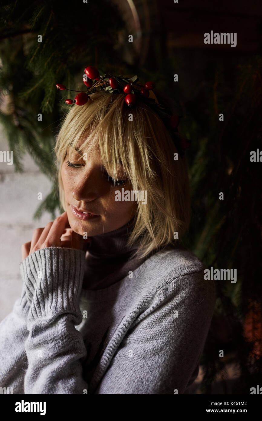 Blond woman, thoughtful, headdress, garland with rose hips, portrait, - Stock Image