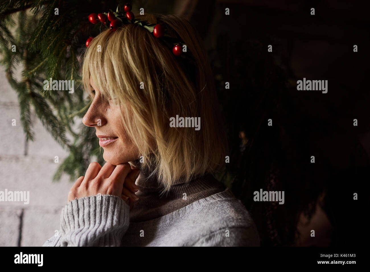 Blond woman smiling, headdress, garland with rose hips, profile, - Stock Image
