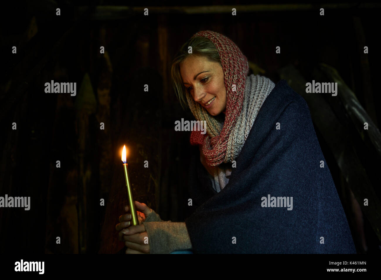 Blond woman holding a candle, smiling, side view, half-portrait, - Stock Image