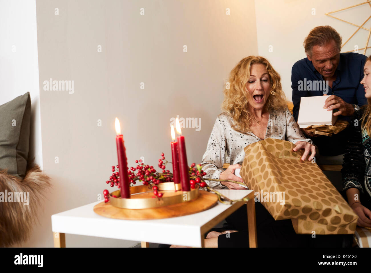 Family at Christmas Eve, unpacking presents, mother surprised, - Stock Image