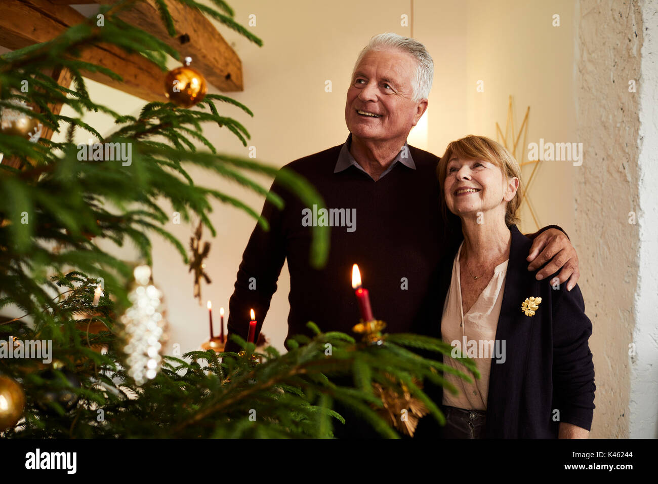 Senior couple in front of Christmas tree, half portrait Stock Photo